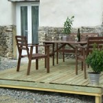 Gite Poppy in Normandy, France. Terrace with wooden garden furniture and barbeque