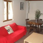 Gite Poppy in Normandy, France. Sitting Room with sofa, coffee table and dining table